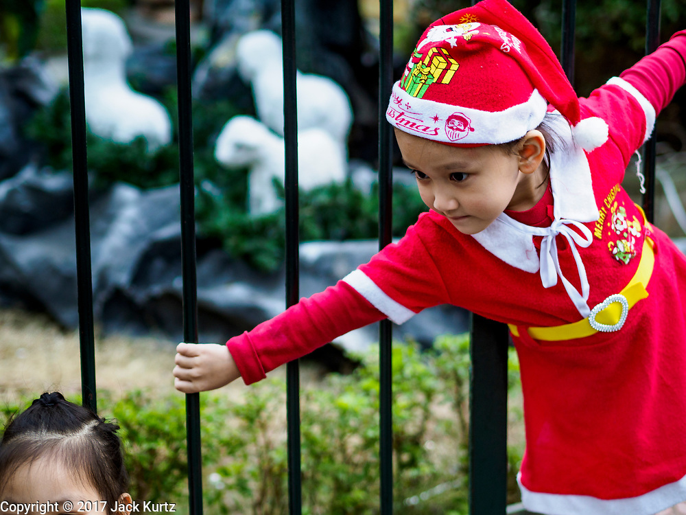 22 DECEMBER 2017 - HANOI, VIETNAM: A child in a Santa Claus outfit plays at St. Joseph's Cathedral in Hanoi while she waits for the Christmas show to start. There are about 5.6 million Catholics in Vietnam. The Cathedral was one of the first structures built by the French during the colonial era and was opened in 1886. It's one of the most popular tourist attractions in Hanoi.   PHOTO BY JACK KURTZ