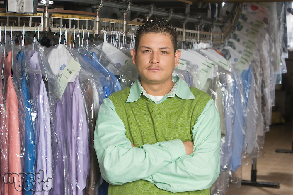 Man working in the laundrette  standing infront of clothes rail