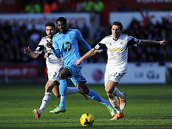 Tottenham Hotspur's Emmanuel Adebayor battles for the ball with Swansea City's Angel Rangel and Swansea City's Jordi Amat - Photo mandatory by-line: Joe Meredith/JMP - Tel: Mobile: 07966 386802 19/01/2014 - SPORT - FOOTBALL - Liberty Stadium - Swansea - Swansea City v Tottenham Hotspur - Barclays Premier League
