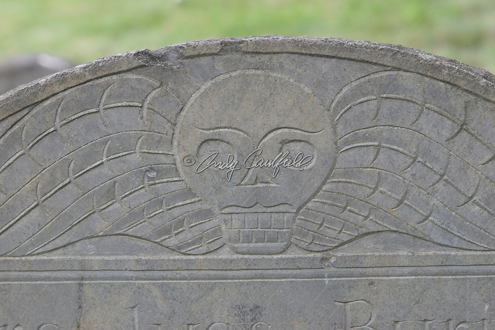 "Headstone detail of winged skull at ""Old Burying Ground"" established in 1635, Cambridge, MA.."