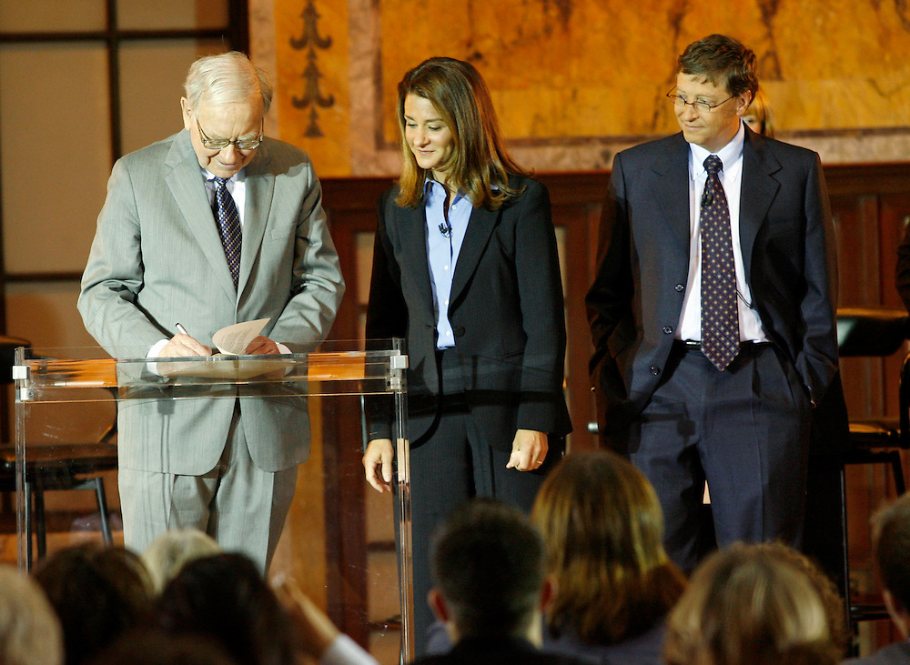 Warren Buffett signs a pledge letter as Melinda French Gates and Bill Gates look on, at the New York Public Library,  Monday, June 26, 2006. (Photo/Stuart Ramson for Bill & Melinda Gates Foundation)