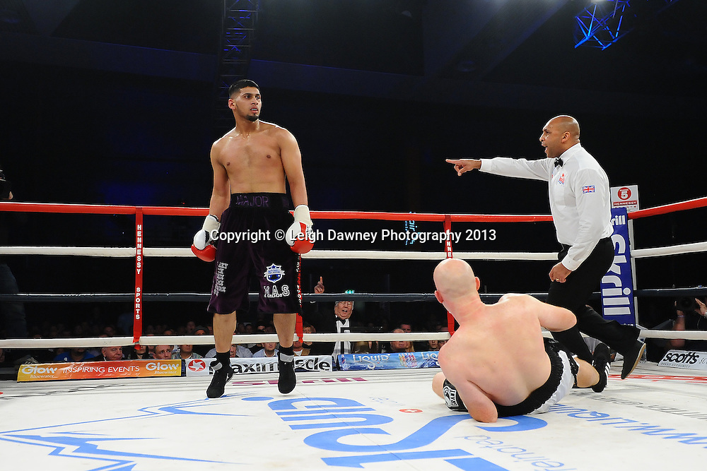 Arfan Iqbal ordered by referee to return to his corner after knocking down Leon Senior during a Light Heavyweight contest. Glow, Bluewater, Kent, UK. Hennessy Sports © Leigh Dawney Photography 2013.