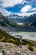 Hike above Mueller Lake on Sealy Tarns Track, in Aoraki / Mount Cook National Park, Southern Alps, Canterbury region, South Island, New Zealand. The peak of Aoraki / Mount Cook (3755 meters / 12,349 feet) rises majestically at the head of Hooker Valley above Hooker Lake in the distance. Glacier-clad Mt Sefton rises on the left. In 1990, UNESCO honored Te Wahipounamu - South West New Zealand as a World Heritage Area.