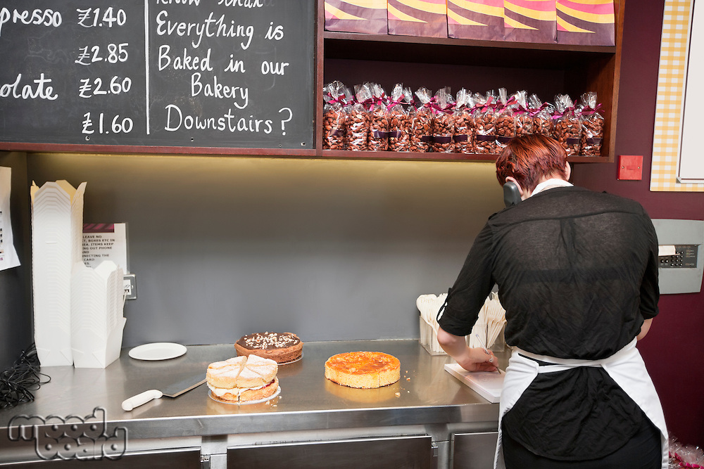 Back view of young attendant working in bakery store