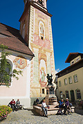MITTENWALD, GERMANY - SEPTEMBER 01, 2010: Unidentified tourists relax next to the statue of Matthias Klotz (the world famous violin maker) in Mittenwald, Germany.