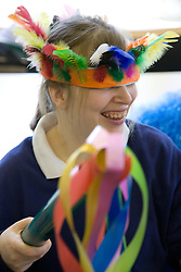 Portrait of young woman Day Service user with learning disability with Indian headdress and coloured paper wand taking part in a music session,