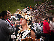 "03 DECEMBER 2011 - PHOENIX, AZ: An Aztec dancer marches in a procession to honor the Virgin of Guadalupe in Phoenix Saturday. The Phoenix diocese of the Roman Catholic Church held its Sixth Annual Honor Your Mother Day Saturday to honor the Virgin of Guadalupe. According to Mexican Catholic tradition, on December 9, 1531 Juan Diego, an indigenous peasant, had a vision of a young woman while he was on a hill in the Tepeyac desert, near Mexico City. The woman told him to build a church exactly on the spot where they were standing. He told the local bishop, who asked for some proof. He went back and had the vision again. He told the lady that the bishop wanted proof, and she said ""Bring the roses behind you."" Turning to look, he found a rose bush growing behind him. He cut the roses, placed them in his poncho and returned to the bishop, saying he had brought proof. When he opened his poncho, instead of roses, there was an image of the young lady in the vision. The Virgin is now honored on Dec 12 in Catholic churches throughout Latin America and in Hispanic communitied in the US.  PHOTO BY JACK KURTZ"