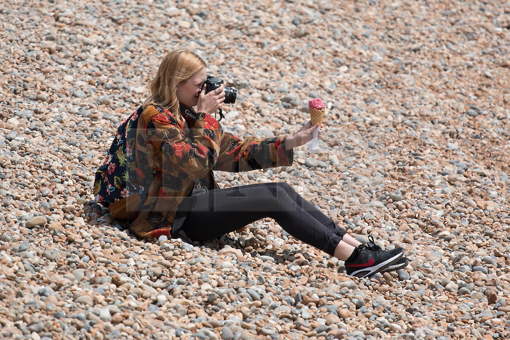 © Licensed to London News Pictures. 01/06/2014. Brighton, UK. A woman photographing an ice cream on Brighton beach. Despite a good start to the weekend on Saturday the weather has deterred some people from coming to the beach. Photo credit : Hugo Michiels/LNP