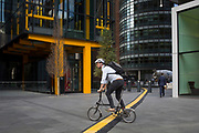 A cyclist crosses a yellow line that covers hazardous electrical cabling at Leadenhall in the City of London, (aka The Square Mile) the capital's financial district, on 2nd September 2019, in London, England.