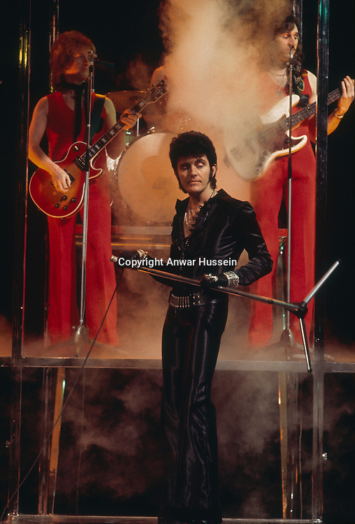 Glam rock singer Alvin Stardust, who first found fame as Shane Fenton, in concert, circa 1975.