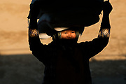 Woman carries heavy load with shaft of light on her face, Monywa, Myanmar