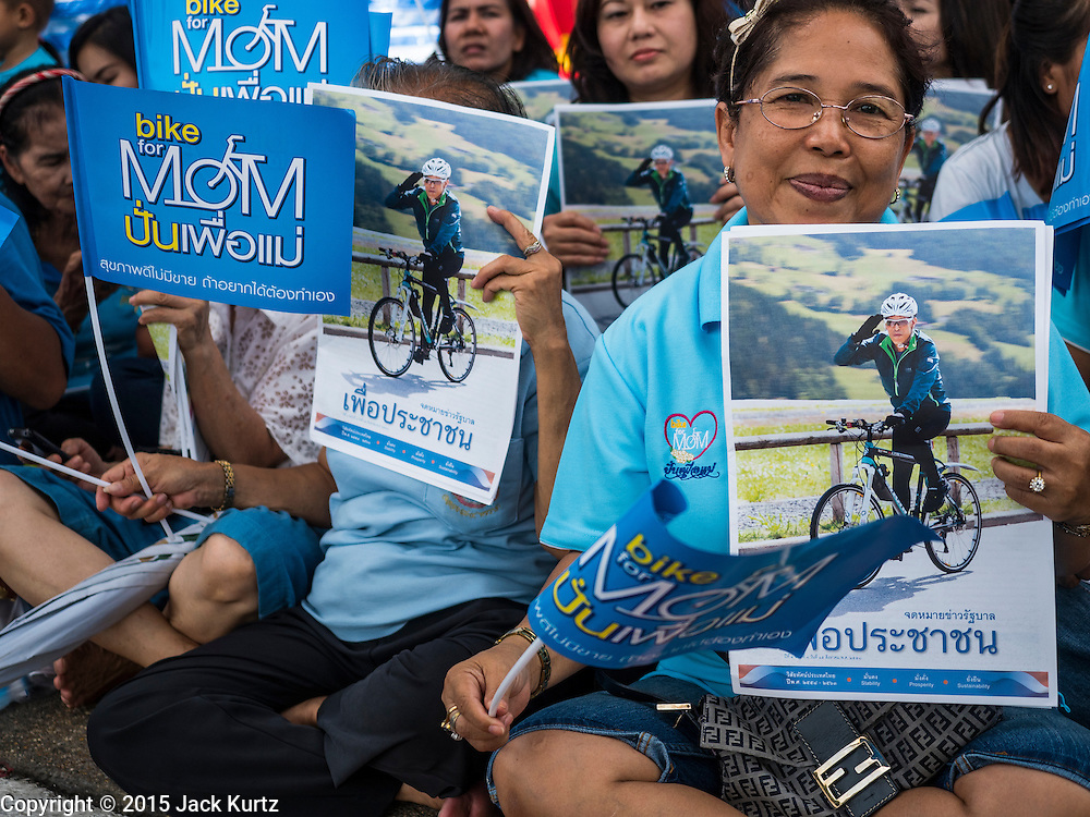 16 AUGUST 2015 - BANGKOK, THAILAND:  People read flyers about the ''Ride for Mom'' while they wait for it to start. The flyers had a photo of His Royal Highness Crown Prince Maha Vajiralongkorn on the back cover. More than 100,000 people across Thailand participated in the Bike For Mom event in honor of Queen Sirikit, who celebrated her 83rd birthday August 12. In Bangkok, the ride was led by His Royal Highness Crown Prince Maha Vajiralongkorn, the Crown Prince of Thailand and Sirikit's only son. Queen Sirikit, who is in poor health and living in a hospital, was unable to attend the bike ride.    PHOTO BY JACK KURTZ