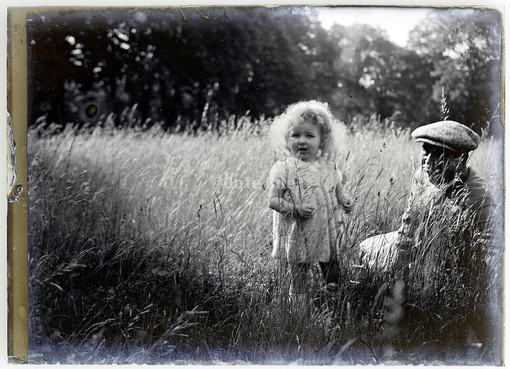 1900s glass plate with toddler and father in field