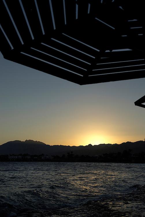 Egypt, Dahab. December/10/2008...The sun sinks below the Sinai mountain range.