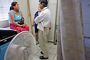 20 JUNE 2009 - PHOENIX, AZ: Mireya Renteria (CENTER BLUE BLOUSE) translates for Dr. Naved Khan (RIGHT) while he talks to Maria Reza (LEFT) in an exam room at the Cultural Cup. The walk in clinic at the Cultural Cup Food Bank started two years ago when Cultural Cup founder Zarinah Awad wanted to expand the food bank's outreach and provide basic medical care for the people who use the food bank. The clinic sees, on average, 7 - 11 patients a week. Awad said that as the economy has worsened since the clinic opened and demand has steadily increased. She attributes the growth to people losing their jobs and health insurance. The clinic is staffed by volunteers both in the office and medical staff. Adults are seen every Saturday. Children are seen one Saturday a month, when a pediatrician comes in. Awad, a Moslem, said the food bank and clinic are rooted in the Moslem tradition of Zakat or Alms Giving, the giving of a small percentage of one's income to charity which is one of the Five Pillars of Islam.   PHOTO BY JACK KURTZ