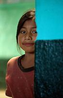 A young schoolgirl peeks behind a wall, Santa Clara, Guatemala.