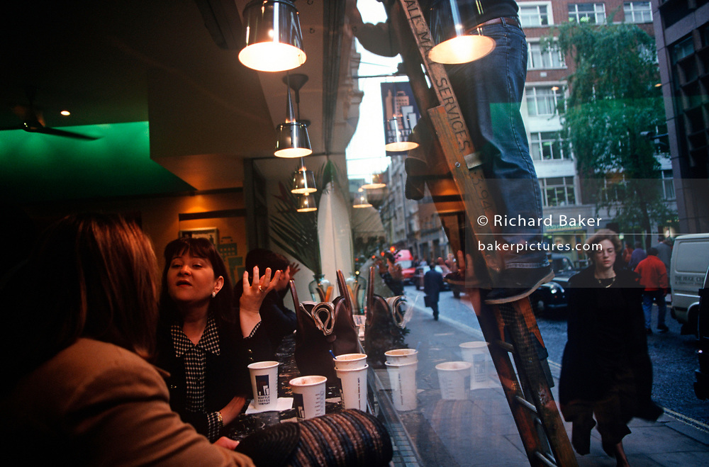 As a 1990s window cleaner stands on his ladders outside in the street, two women talk in the window of a branch of Seattle Coffee Company the City of London (aka The Square Mile), the capital's financial centre, on 21st June 1997, in London, England. (Photo by Richard Baker / In Pictures via Getty Images)