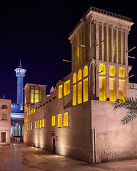 Historic Houses in the Bastakiya Quarter, Dubai are colourfully lit at night.