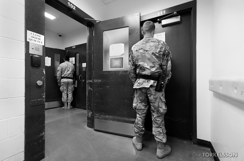 Military guards at the prison camp at Guantanamo, Cuba, Jan 28 2017, guards an entrance to a cell block.<br /> The guards turn away their faces so you cannot identify them. It is standard operation procedure when pictures are made. When you work as a journalist at the Guantanamo you work under military censorship and all your material is checked every day and approved for publication.<br /> The prison camp on the Guant&aacute;namo naval base was the creation of President George W. Bush. The prison camp was considered an important part of the US war on terrorism. Over the years, 779 people have been brought to the camp. 41 people are still detained. Of them, 26 people count as &quot;forever prisoners&rdquo;, indefinite detainees under the Law of War. Two prisoners have been in the camp since it was opened in January 2002. The last prisoner taken to the camp came in March 2008. The so-called war on Terror and the Guantanamo prison camp have been heavily criticized for violation of human rights regarding torture and habeas corpus.<br /> It is unclear what US President Donald Trump wants to do with the camp, but during the election campaign he said that he would fill Guant&aacute;namo Bay with &quot;bad dudes&quot;. Photo by Ola Torkelsson<br />