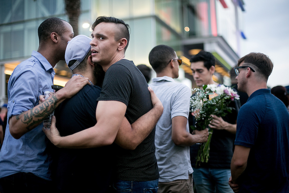 ORLANDO - JUNE 13, 2016: A group embraces during a candlelight vigil outside the Dr. P. Phillips Center for the Performing Arts in Orlando, Florida. CREDIT: Sam Hodgson for The New York Times.