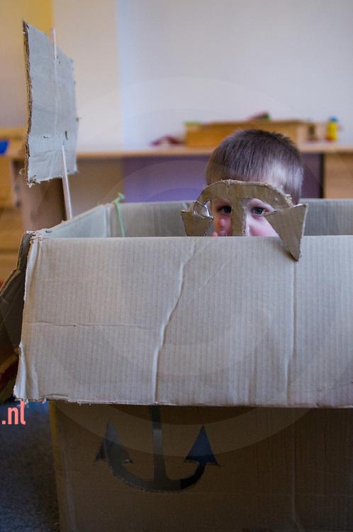 een kleuter speelt in / met een zelfgemaakte boot van karton