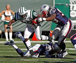 Sept 20, 2009; East Rutherford, NJ, USA;  New York Jets running back Leon Washington (29) avoids a tackle by New England Patriots defensive end Mike Wright (99) and New England Patriots cornerback Darius Butler (28) during the second half at Giants Stadium. The Jets defeated the Patriots 16-9.