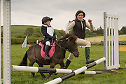 In hand, a mother leads her daughter in her first pony club event.