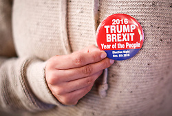 "© Licensed to London News Pictures. 09/11/2016. New York City, A woman holds a badge reading ""2016 TRUMP, BREXIT, Year of the People"" while watching election coverage in Times Square, New York City, on Wednesday, 9 November. Photo credit: Tolga Akmen/LNP"
