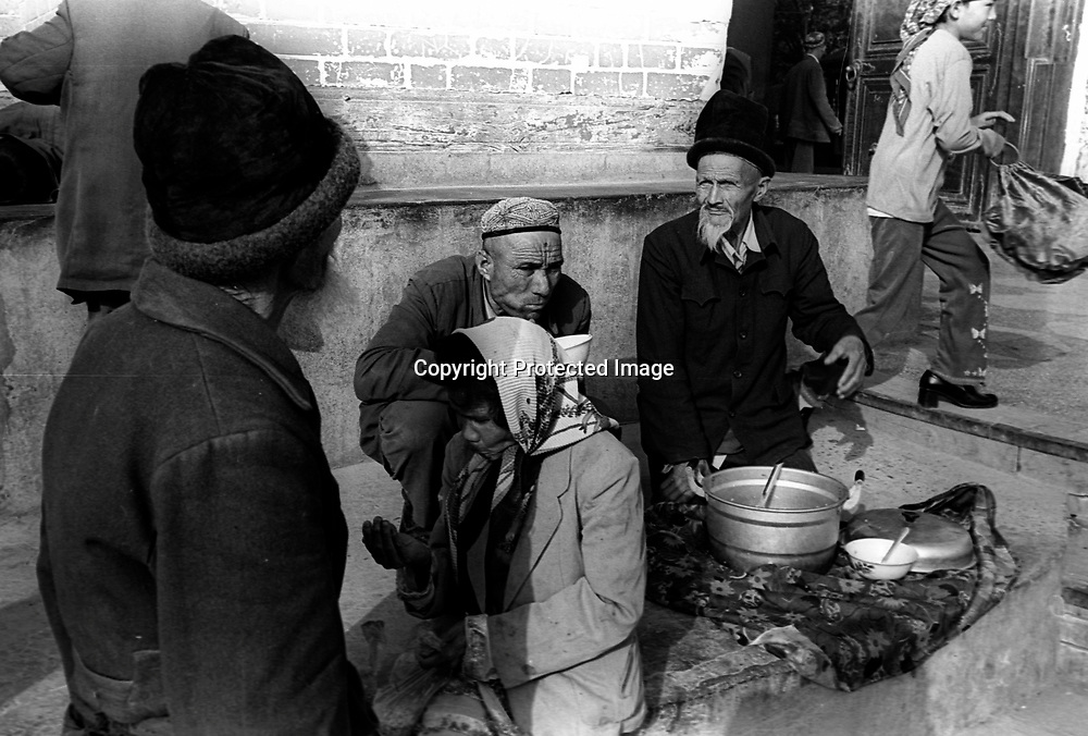 KASHGAR,1 OCOTBER 2001: beggars share a pot of porridge outside the main mosque in Kashgar. Uighur muslims in China's western Xinjiang province mostly stick to islamic lifestyles due to their proximity to Afghanistan & Pakistan .Uighur muslims in southern Xinjiang province lead very basic lifestyles and have an average monthly income of about 50 US$..Today, 47 percent of Xinjiang is Uighur and 41 percent is Han. Smaller groups of other Turkic Muslims, including Kyrgyz, Kazakhs, Tajiks and Uzbeks, make up the remainder of the population ..The government maintains tight control over Uighur culture.All mosques are required to register with the government. In 2001, authorities called in 8,000 imams for special training on the Communist Party's ethnic and religious policies. In 2002, Xinjiang's top university eliminated all instruction in the Uighur language. .