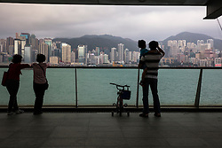 Small group of people viewing the Hong Kong, China skyline and mountains across Victoria Harbor.