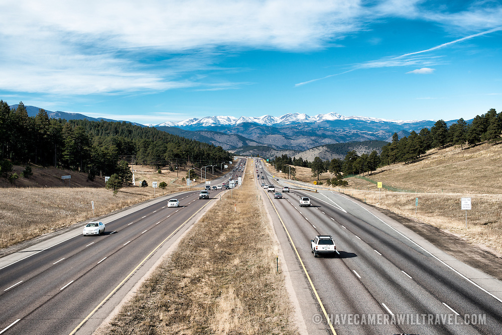 A highway leads to the snow-capped Rocky Mountains in the distance near Golden, Colorado, just outside Denver.