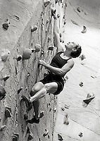 Woman practicing rock climbing in indoor facility (B&W) low angle view (focus on face).