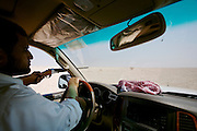 Mr. Hamad hunting pigeons for his falcons with a shotgun in his Toyota Landcruiser.