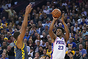 January 31, 2019; Oakland, CA, USA; Philadelphia 76ers guard Jimmy Butler (23) shoots the basketball against Golden State Warriors center Kevon Looney (5) during the second quarter at Oracle Arena.