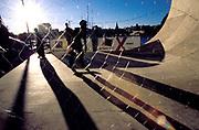 Three men skateboarding behind a mesh fence. Kristiansands Norway 2000