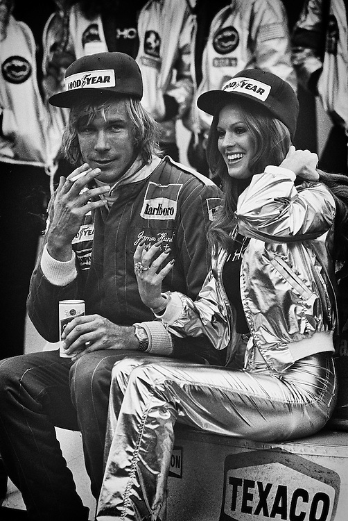 British 1976 World Champion James Hunt, a Schlitz and cigarette in hand and Penthouse Pet by his side, relaxes on his still warm Marlboro McLaren M26 after winning the 1977 United States Grand Prix at Watkins Glen. <br />