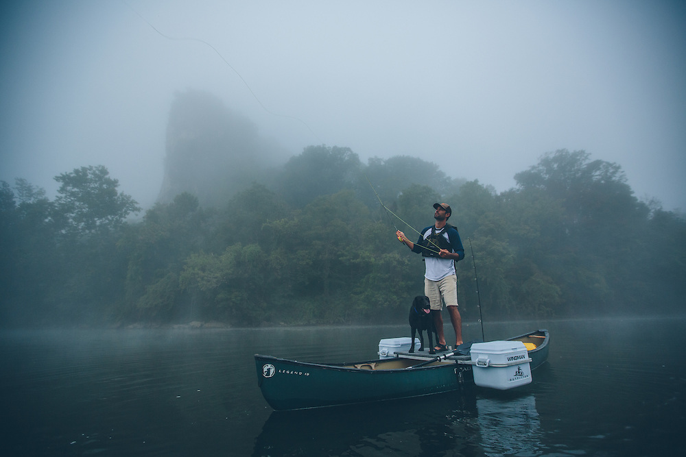 The wingman outfitter and man fishing with dog from canoe and in stream for rainbow trout in Virginia in the Blue Ridge Mountains.