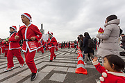 Spectators wave as participants take part in the Tokyo Great Santa Run in Komazawa-daigaku Olympic Park, Tokyo, Japan. Sunday December 22nd 2019, The great Santa Run was first run in Tokyo in 2018. This years run saw over 3,000 people in Santa costumes run and walk a 4.3 kilometre course to raise money for medical charities in japan and water projects for the Maasai in Kenya.