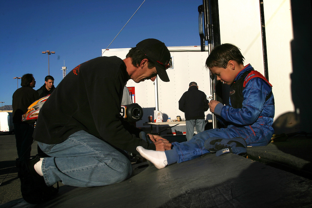 Chris Trickle 6 get help from Michael Tompson to tie his shoes before the race in Primm Nevada on Saturday march 3 .2007.
