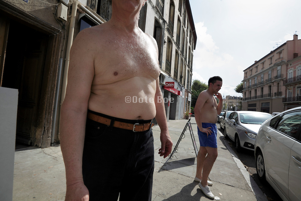 two bare breasted men on a sidewalk