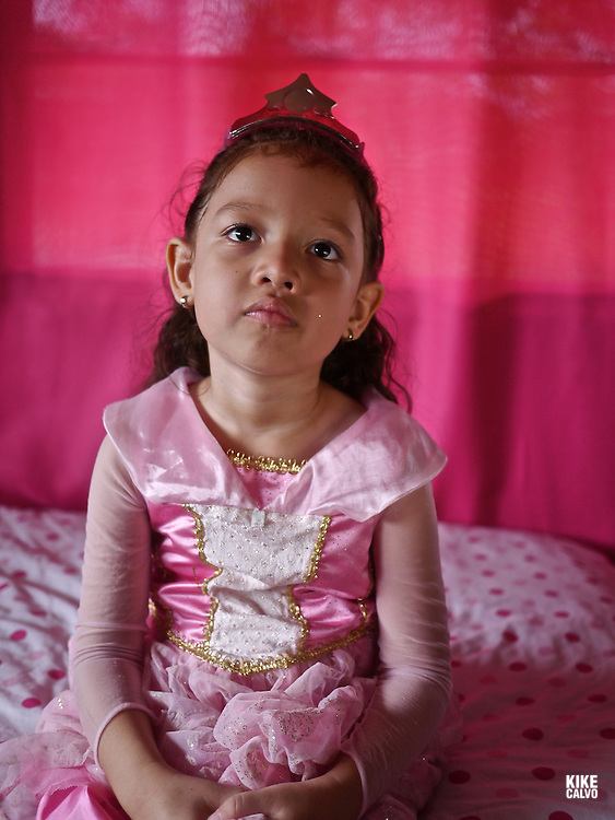 Latin girl dressed as a princess in a pink room