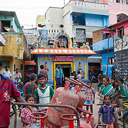 People gather near the entrance of a slum in Saidapet, Chennai, India.  This area is one of 40 out of 132 slums in which Janodayam works. Founded in the 1980s by two Jesuit priests, Janodayam works with the Dalit caste, formerly known as 'untouchables'.  The NGOs goal is to help are numerous and educating children, teaching women how to have self sustaining businesses, and to end the practice of Dalits cleaning manholes, public latrines, and waste in public places (referred to as manual scavenging) are among their top goals. Photographs commissioned for the Opus Prize Foundation.