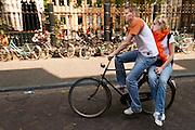 Een jongen is met een meisje achterop de fiets op weg naar het feest op het Domplein. In Utrecht wordt volop Koninginnedag gevierd met een vrijmarkt, bandjes, bootjes en gewoon lekker liggen in de zon.<br /> <br /> A boy is cycling with a girl on a bike to the party at Queensday in Utrecht.