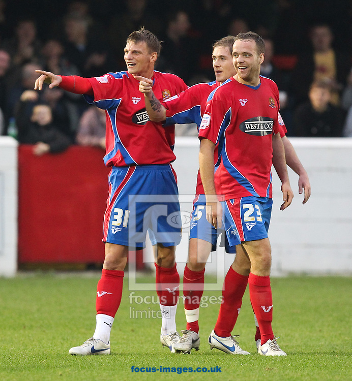 Picture by John Rainford/Focus Images Ltd. 07506 538356.12/11/11.Brian Woodhall, 23, of Dagenham & Redbridge celebrates their equaliser with Phil Walsh and Richard Rose against Bath City during the FA Cup 1st round match at Victoria Road stadium, Dagenham.