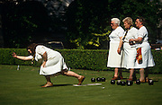 A trio of elder ladies dressed in whites watch a younger club member demonstate how to play bowls on a perfect London lawn