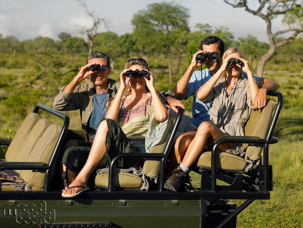 Group of tourists on safari sitting in jeep looking through binoculars