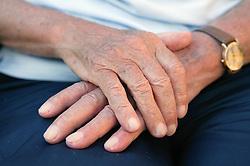 Elderly mans hands on lap,