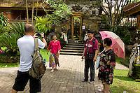 Tourist having photograph taken at the Palace Ubud. Bali revisited January 2012.