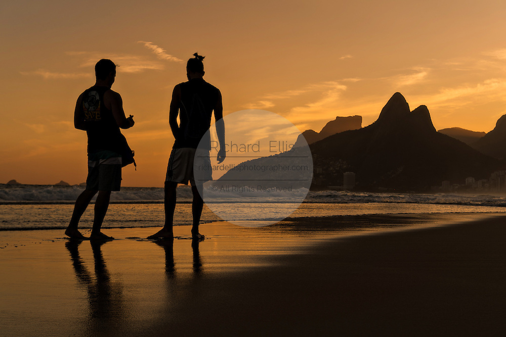 Young men silhouetted by sunset on Ipanema Beach with the Two Brother mountains in the distance in Rio de Janeiro, Brazil.