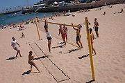 An aerial view of a beach volleyball game, played by young, fit people on the sand at a seaside, on 12th July 2016, at Cascais, near Lisbon, Portugal. A young woman leaps prematurely to block an oncoming serve by her opposition team. Cascais is a coastal town and a municipality in Portugal, 30 kilometres (19 miles) west of Lisbon. The former fishing village gained fame as a resort for Portugal's royal family in the late 19th century and early 20th century. Nowadays, it is a popular vacation spot for both Portuguese and foreign tourists and located on the Estoril Coast also known as the Portuguese Riviera. (Photo by Richard Baker / In Pictures via Getty Images)